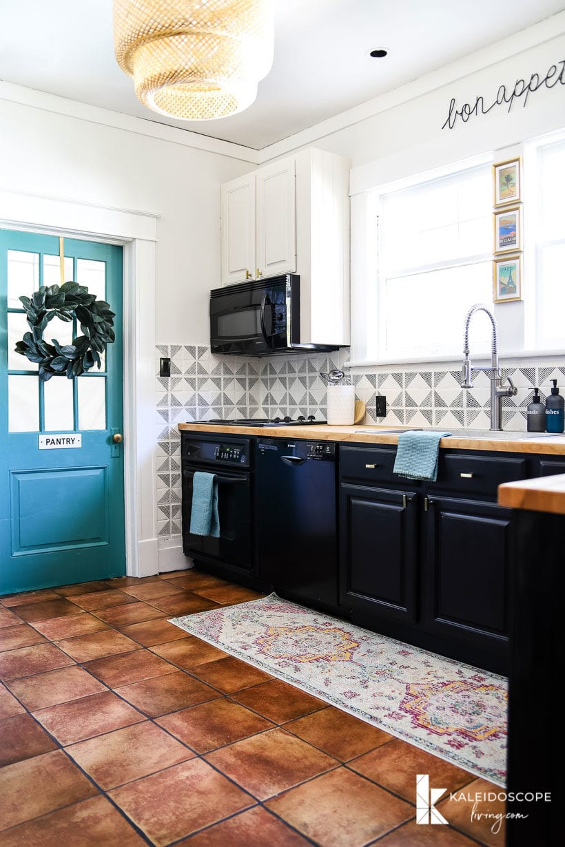 kitchen with terra cotta floors, black and white cabinets, and turquoise accents