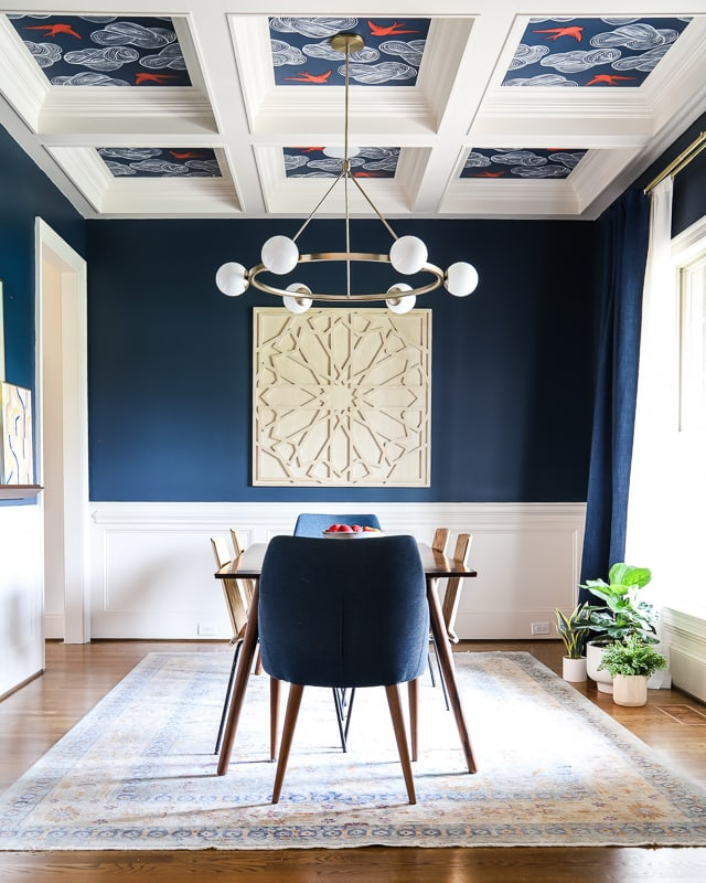 navy blue dining room with wallpaper ceiling